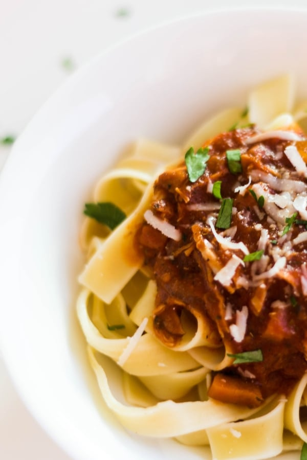 Pappardelle pasta topped with pork ragu with a sprinkling or parmesan reggiano cheese and fresh parsley