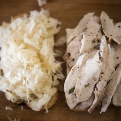 A delicious turkey reuben in the assembly process with sauerkraut on one side and turkey pieces on the other slice of bread