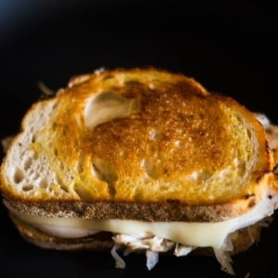 A delicious turkey reuben on a cast iron grill with melting swiss cheese!