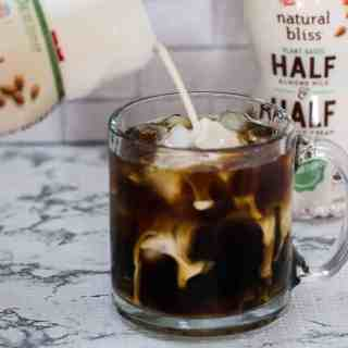 delicious iced coffee with natural bliss creamer being poured into the coffee