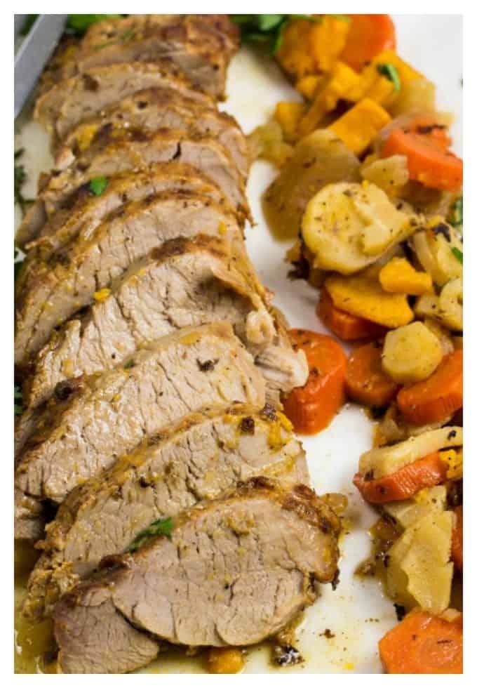 sliced pork tenderloin with sweet potatoes, white potatoes, and carrots on a long white platter.