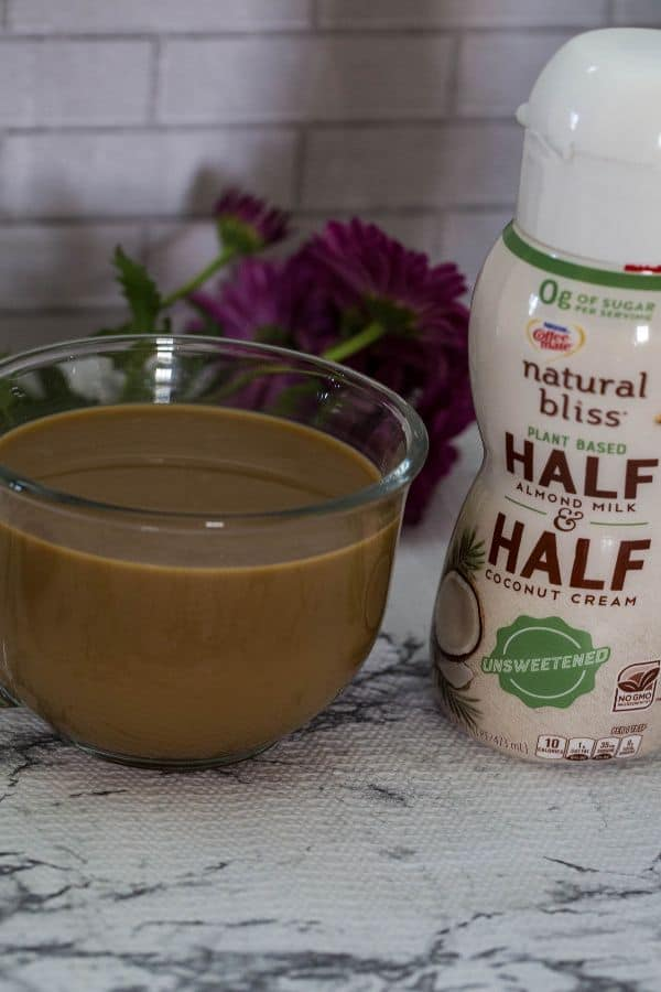 natural bliss half and half plant-based creamer and a coffee to the side in a clear glass mug