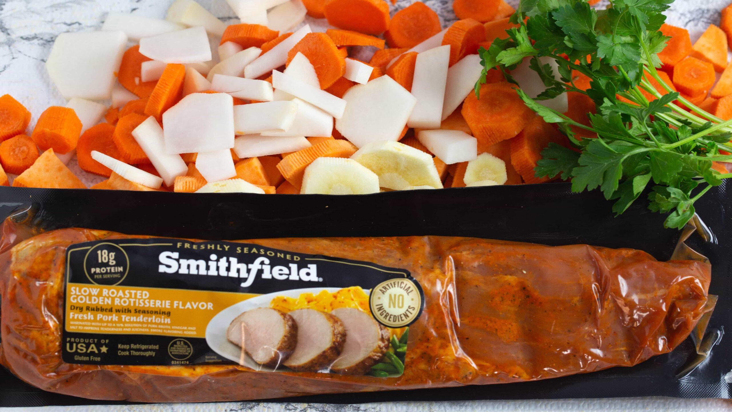 Smithfield marinated pork tenderloin with root veggies including sliced parsnips and carrots getting ready for to be pressure cooked.