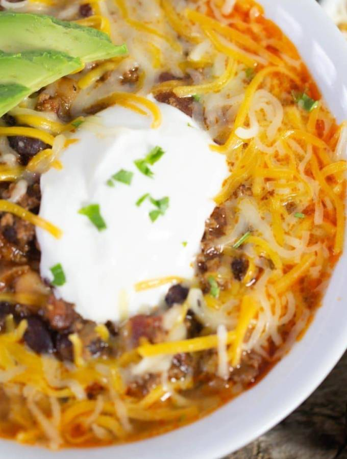 Delicious chipotle chili in a white bowl topped with Mexican shredded cheese melting into the chil. A dollop of sour cream and chopped cilantro.