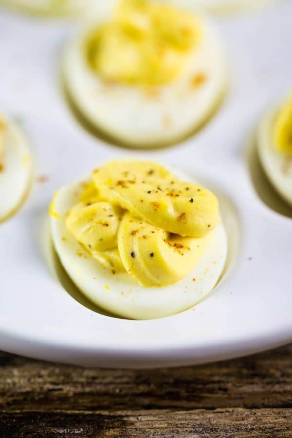 mouthwatering horseradish deviled eggs on an egg platter with a sprinkle of black pepper on top of the deviled egg.