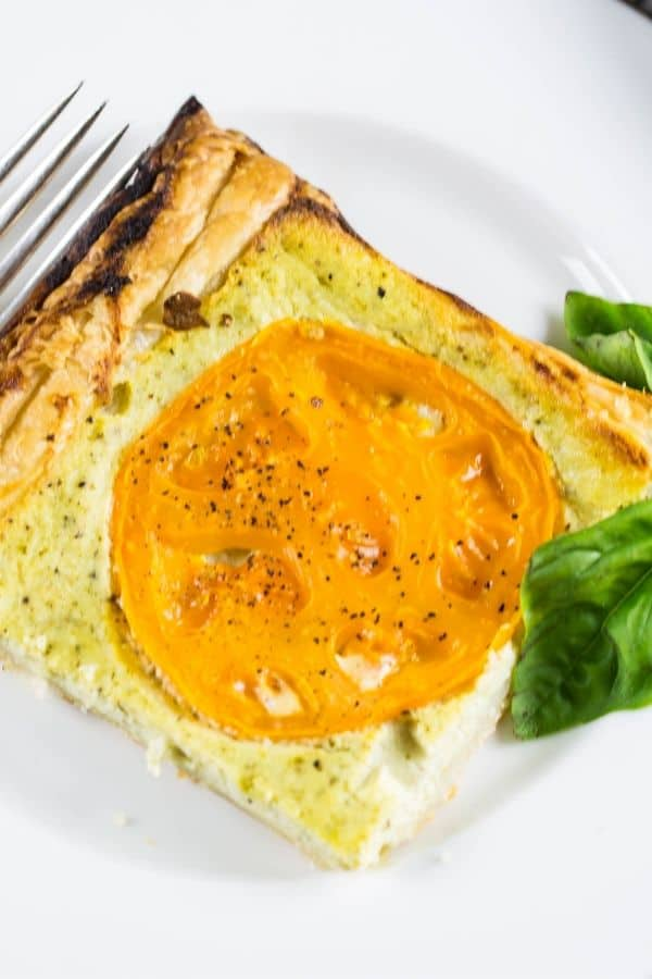 A slice of ricotta tomato tart filled with a ricotta cream with pesto.