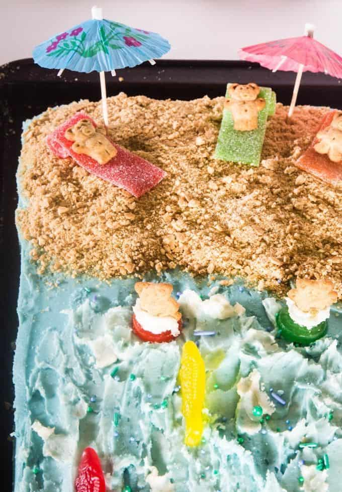 Festive beach cake topped with teddy grahams, tiki umbrellas