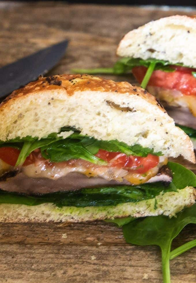 portobello mushroom burger cut in half with fresh spinach and tomatoes on a wooden cutting board