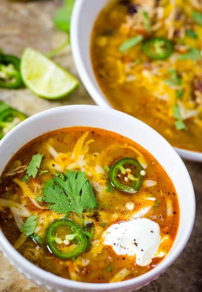 Slow cooker chicken enchilada soup in a white bowl topped with shredded cheese, jalapenos, and cilantro.