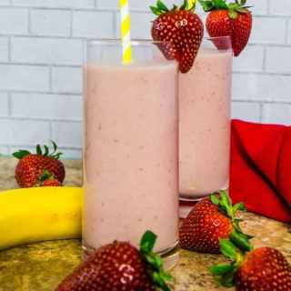 strawberry banana smoothie in clear tall glasses topped with strawberries and yellow straw.
