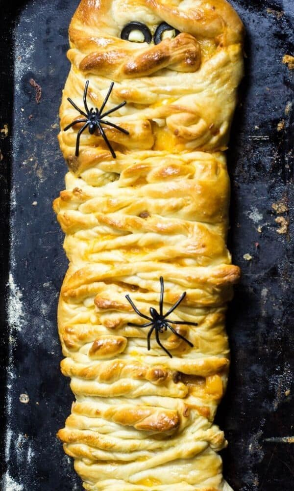 Festive taco meat mummy bread with fake spiders on the dough.