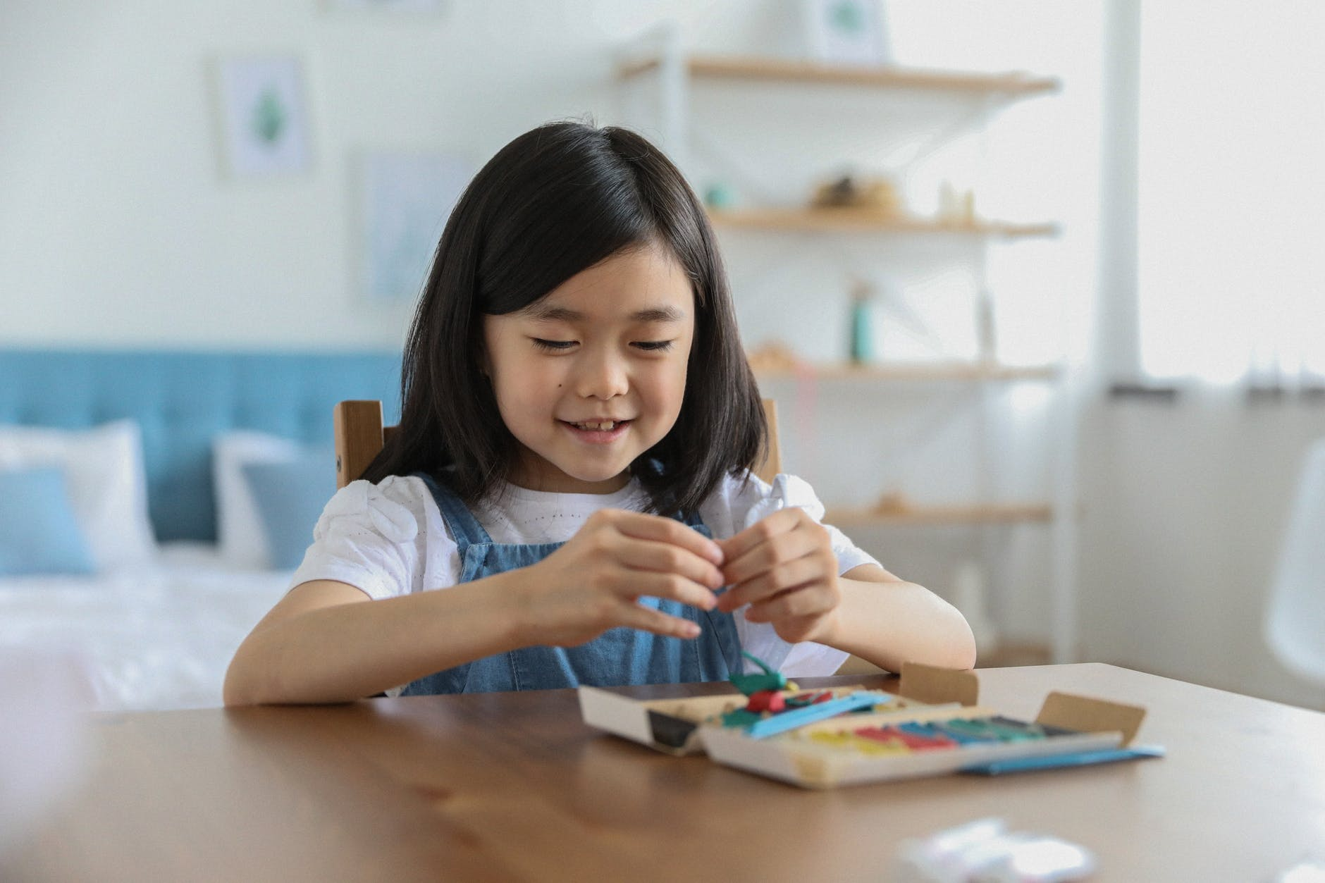 cute happy asian girl sculpting from plasticine