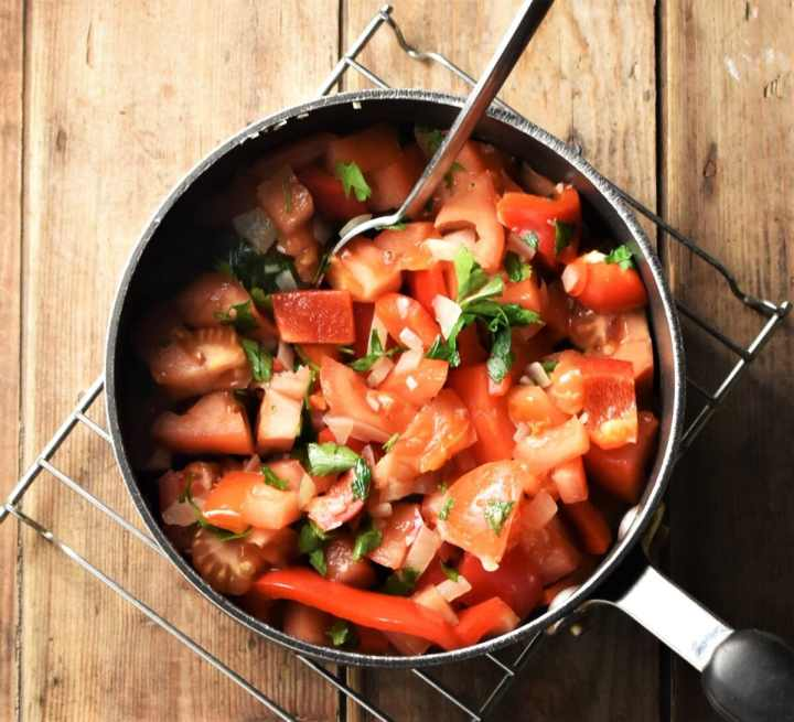 Chopped tomatoes, peppers and herbs in pot with spoon.