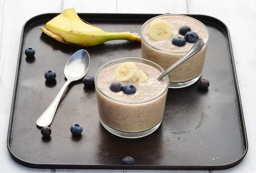 Overnight quinoa with banana slices and blueberries in 2 cups with spoon, another spoon, blueberries and banana peel on dark table.