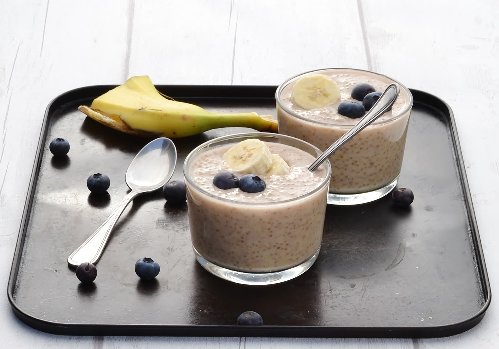 Side view of overnight quinoa with banana slices and blueberries in 2 cups with spoon, another spoon, blueberries and banana peel on dark table.