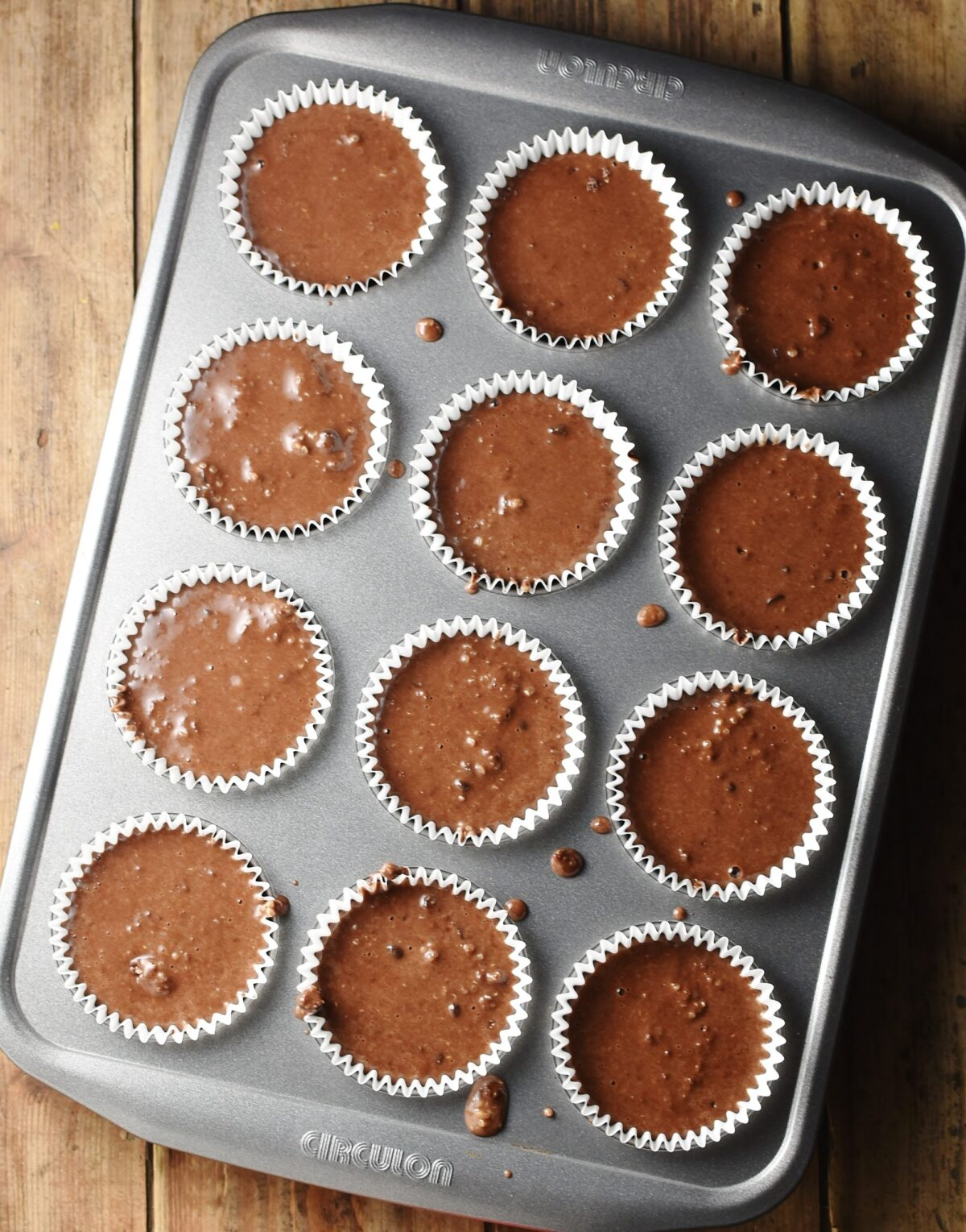 12 unbaked chocolate muffins in white paper cases in muffin pan.
