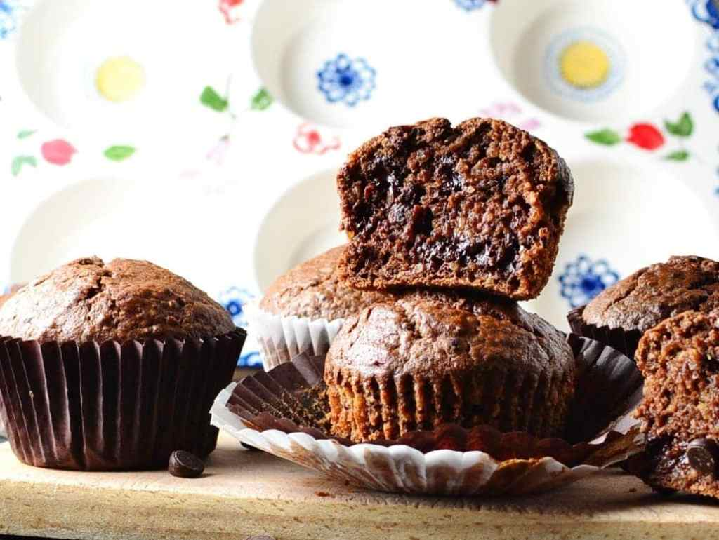 Side view of protein chocolate muffins with paper cases on wooden board with ceramic muffin dish in background.