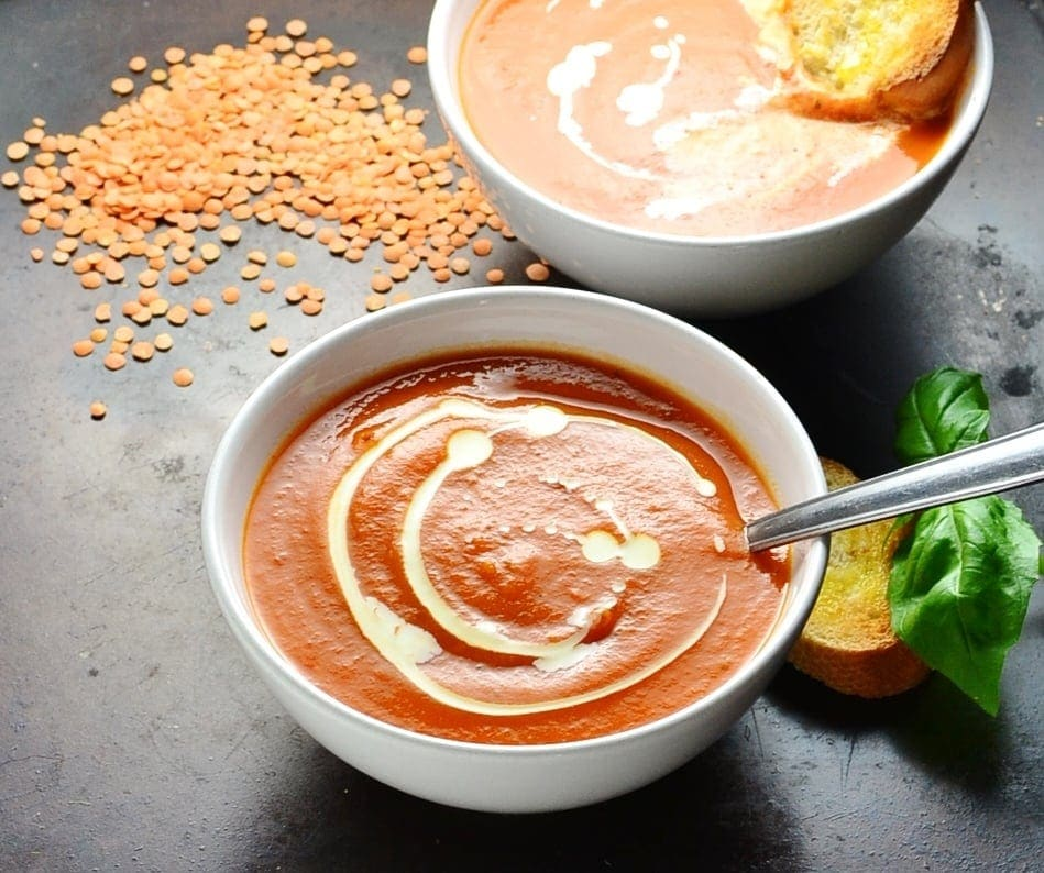 Side view of tomato and lentil soup in white bowls with spoon, red lentils, basil and toast on black background.