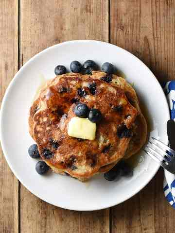 Stack of blueberry pancakes on white plate with blue-and-white cloth with fork and knife to the right.