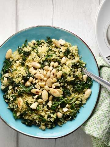 Top down view of bulgur wheat with kale and almonds in blue bowl with spoon, with green cloth and plate with forks and capers to right.
