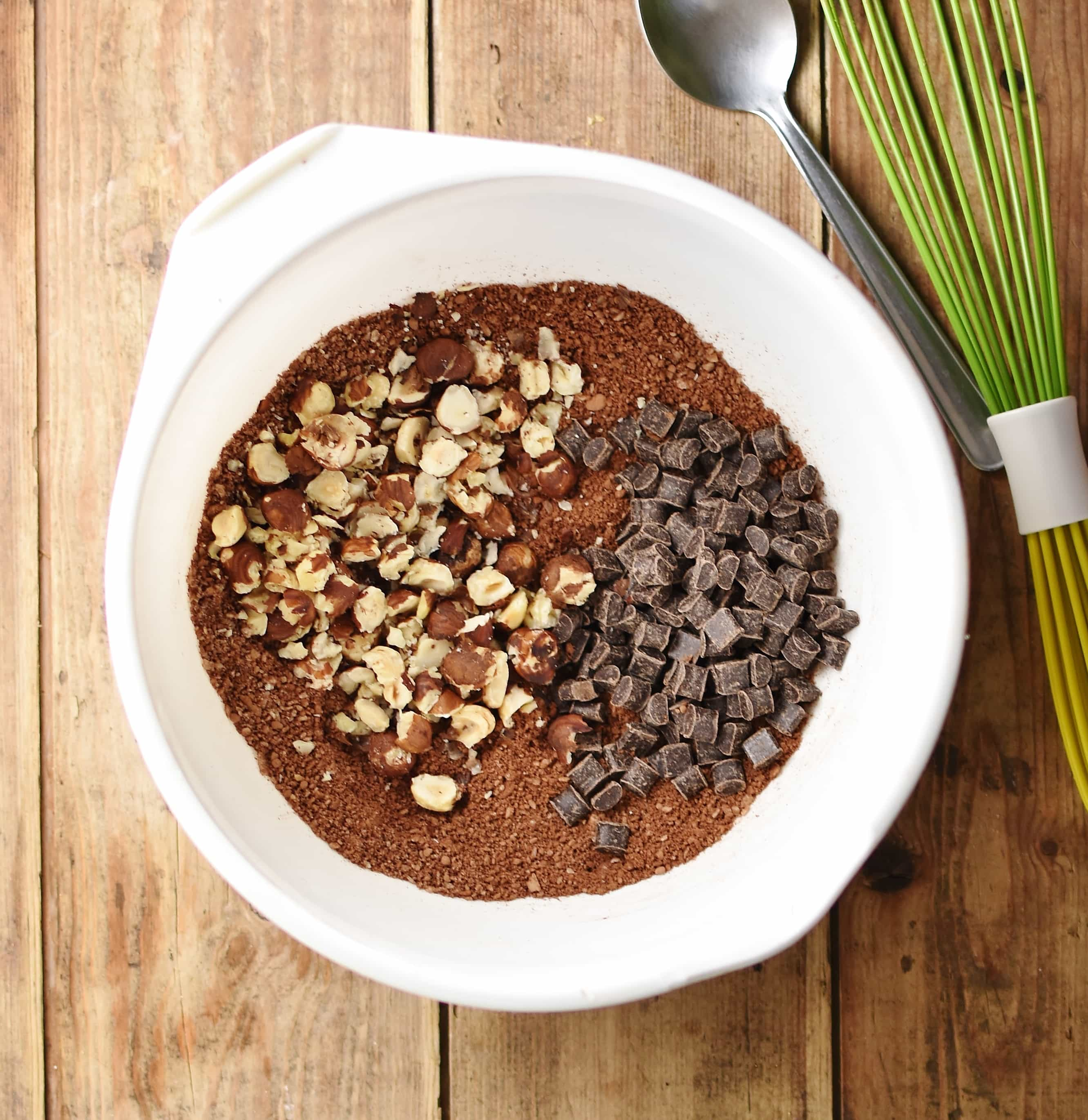 Cocoa mixture with crushed nuts and chocolate chunks inside large white bowl with spoon and green whisk in top right.