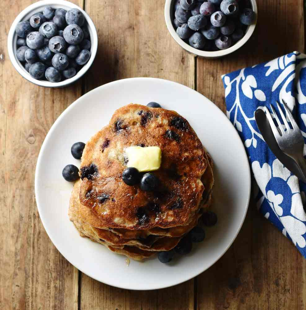 Blueberry pancakes stacked on top of white plate, with blueberries in 2 dishes and blue-and-white patterned cloth in background.