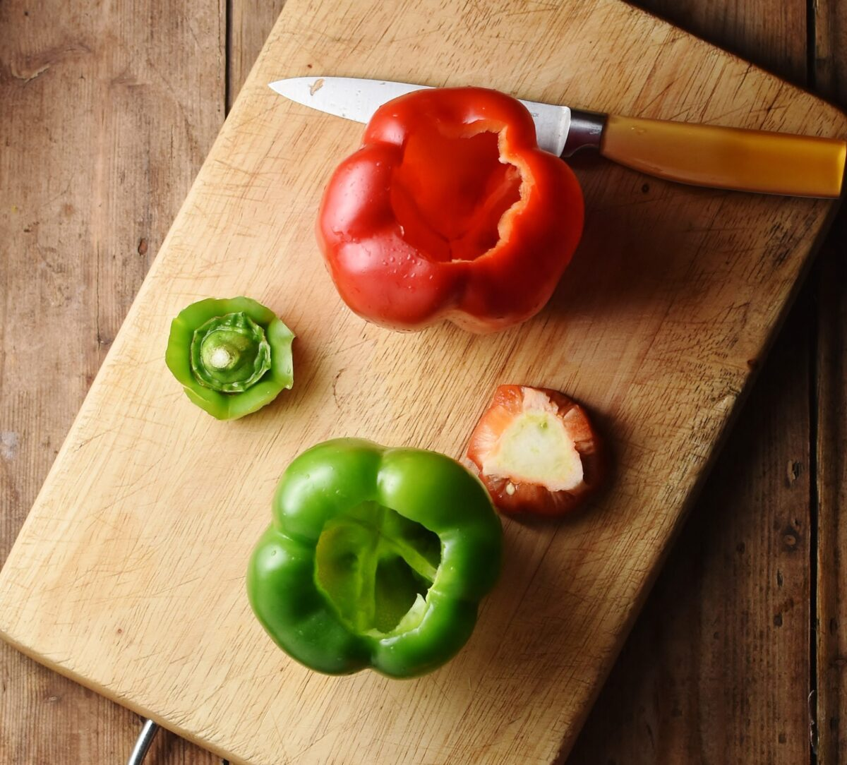 Red and green bell peppers tops removed on chopping board with small yellow knife.