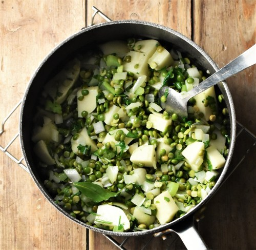 Split green peas and cubed potatoes in pot with spoon.
