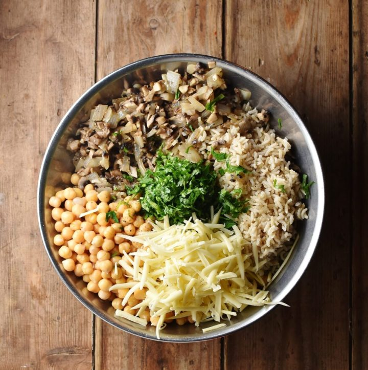 Chickpeas, mushrooms, brown rice, grated cheese and chopped herbs in large metal bowl.
