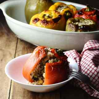 Red stuffed pepper with rice in white bowl with fork, checkered red-and-white cloth to the right and stuffed peppers in dish in background.