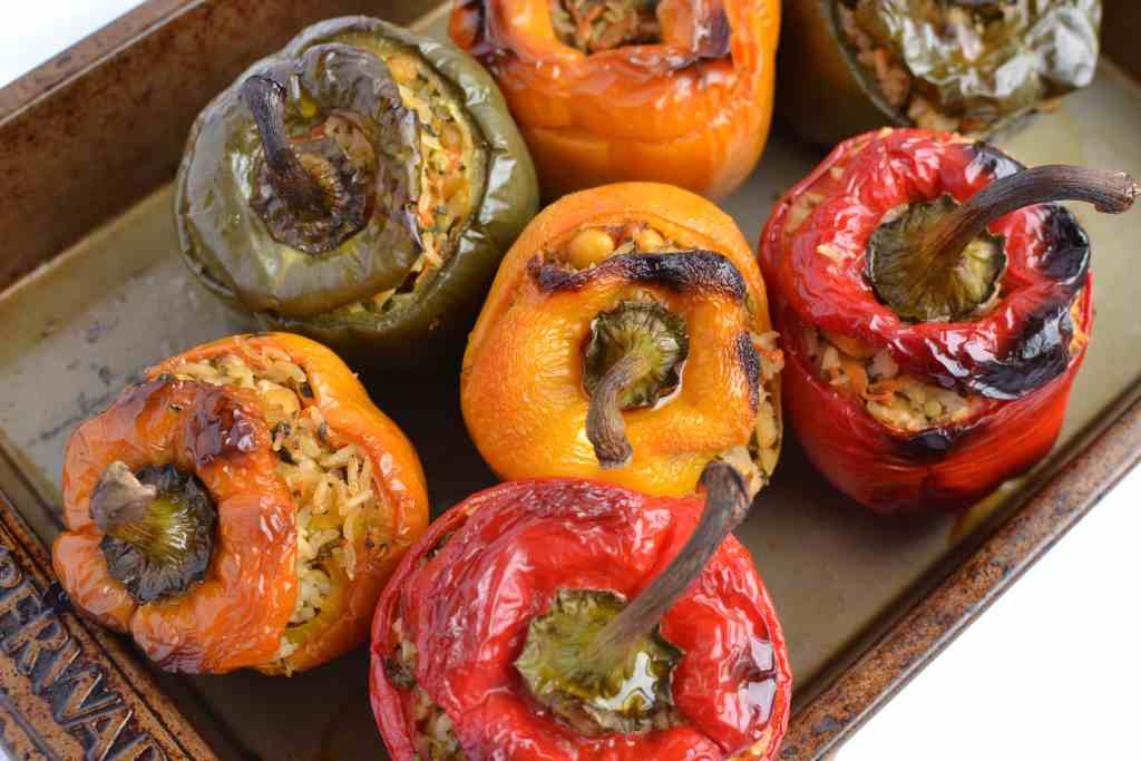 Green, yellow and red stuffed peppers in oven tray.