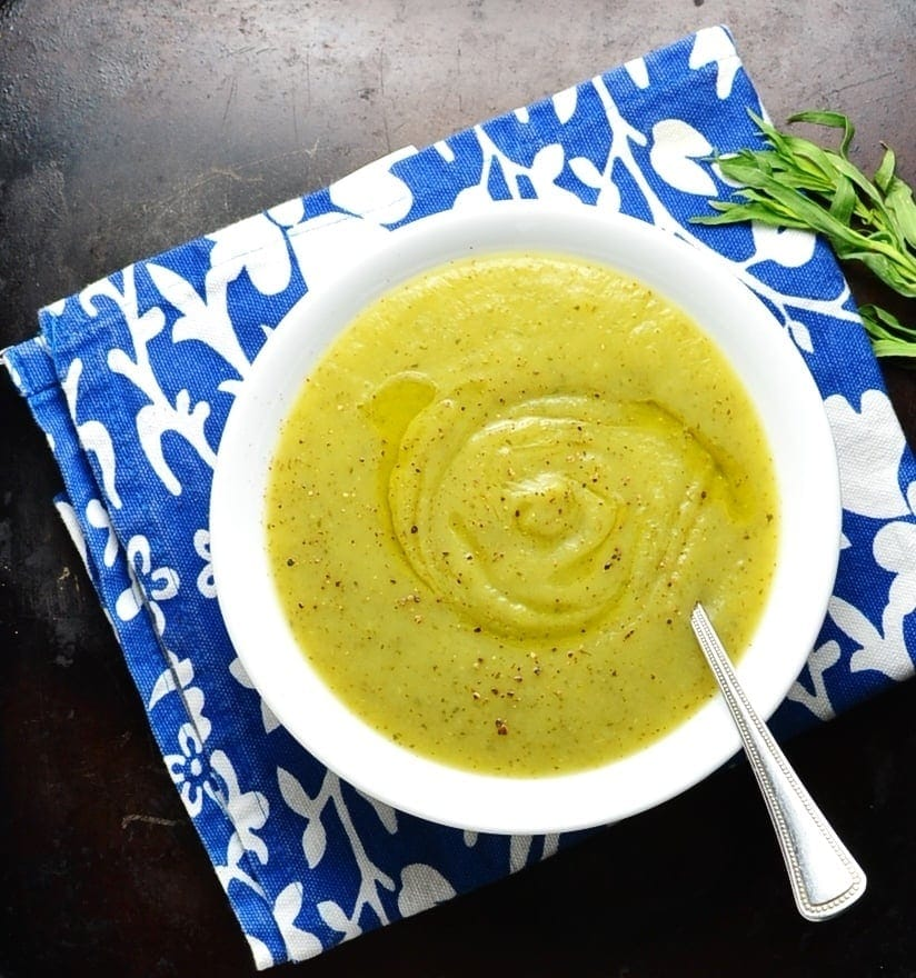 Top down view of easy zucchini soup in white bowl with spoon on blue cloth.