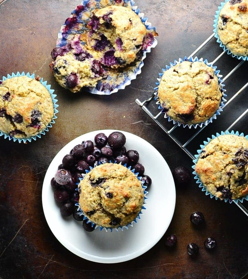 Top down view of blueberry quinoa muffins on top of dark surface with small white plate and cooling rack.