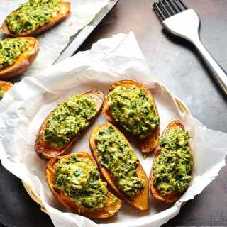 Top down view of stuffed sweet potatoes with spinach in basket lined with white paper and cooking brush next to it.