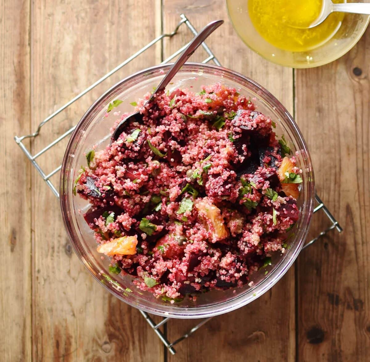 Top down view of quinoa beetroot salad with spoon inside large bowl, with dressing in small dish in top left corner.