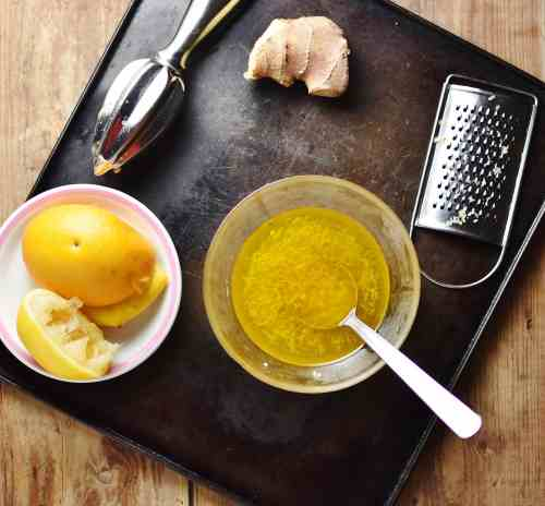 Salad dressing with spoon in bowl, zester, ginger, juicer and orange on top of small white plate.