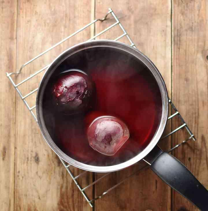 2 beets in water inside saucepan on top of cooling rack.
