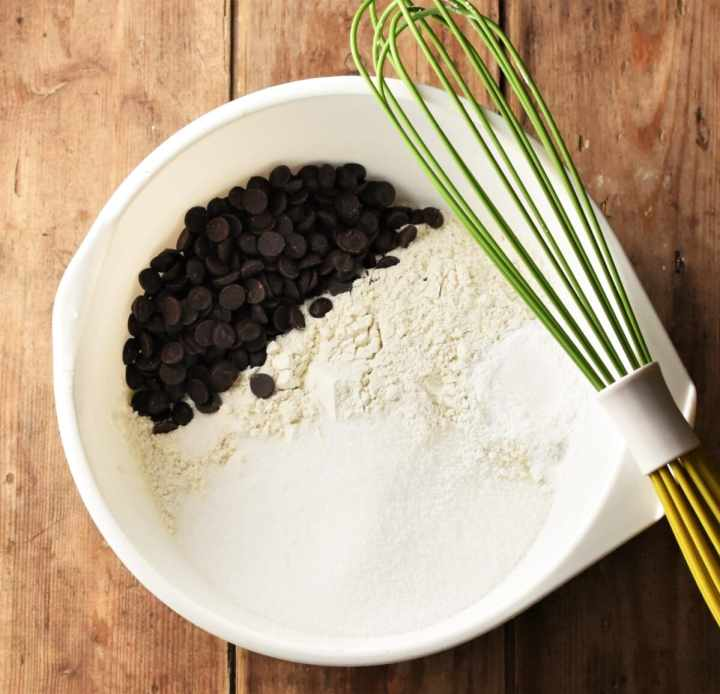 Flour mixture and chocolate chips in large white bowl with green whisk on top.