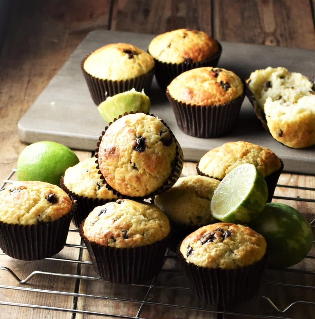 Chocolate chip muffins on rack and grey wooden board with limes.