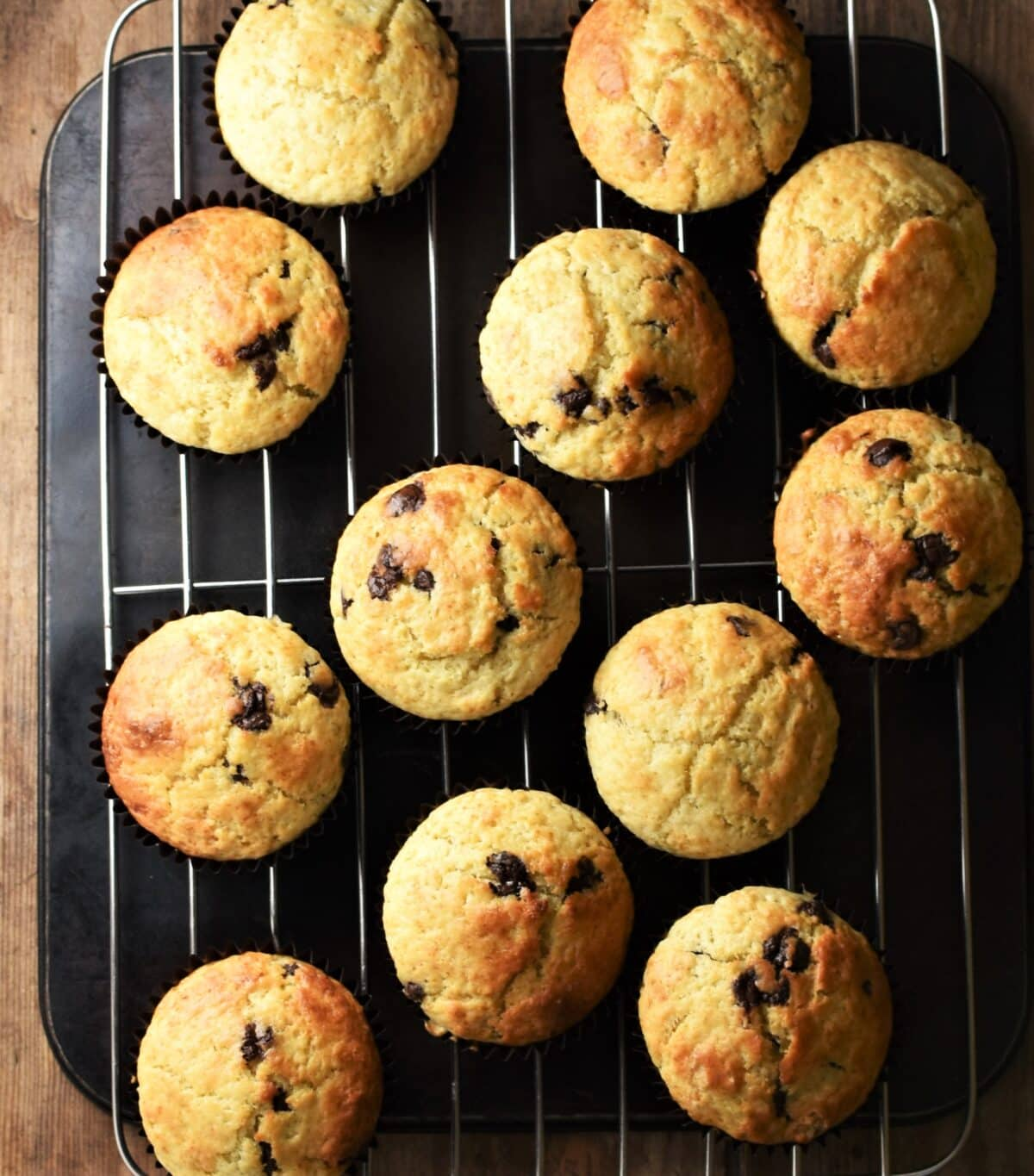 Lime chocolate chip muffins on top of rack and black tray.