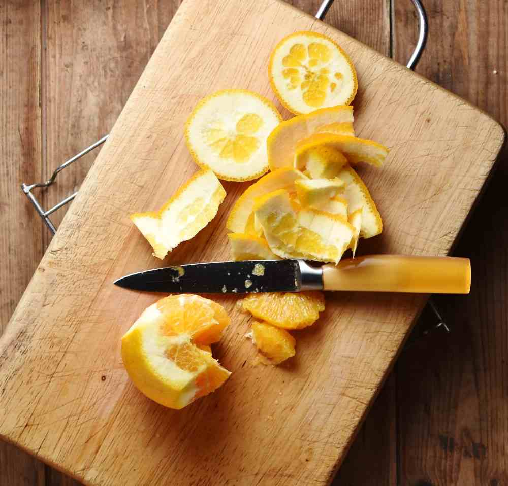 Peeled orange with knife on top of cutting board.