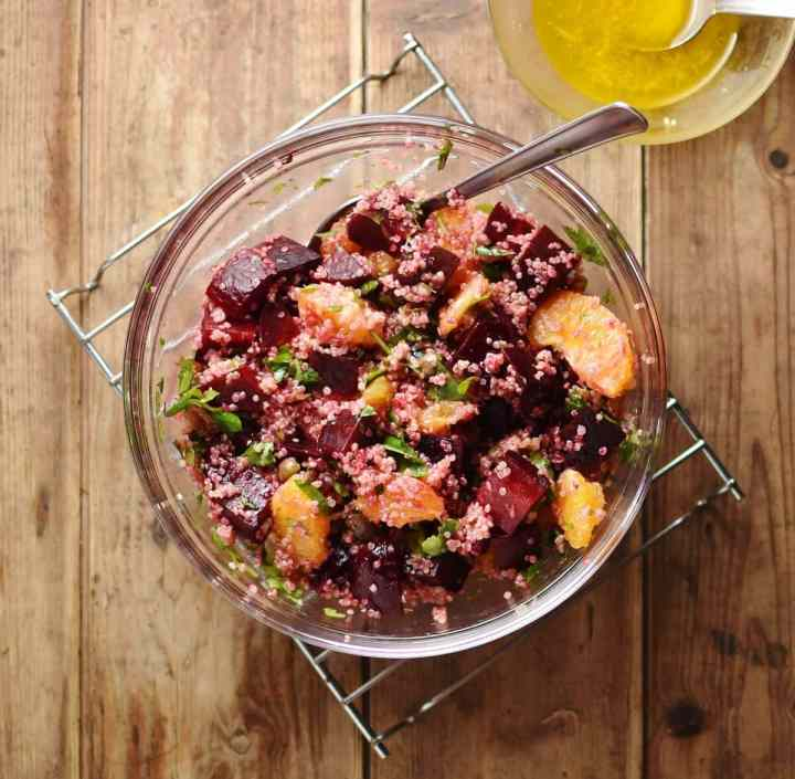 Beets, quinoa and orange salad with spoon inside translucent bowl with salad dressing in small dish in top right corner.