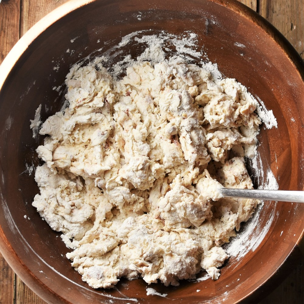 Bread dough mixture in wooden bowl with fork.