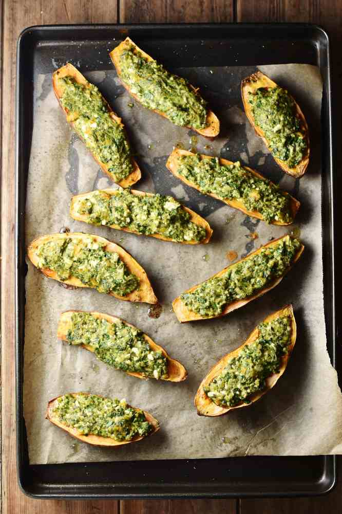 Spinach stuffed sweet potatoes on top of baking sheet lined with paper.