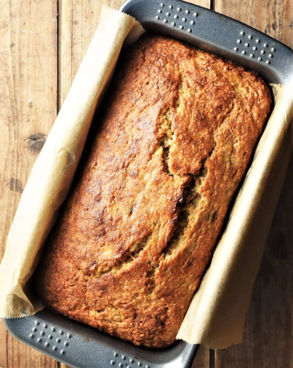 Top down view of banana bread in pan lined with paper.