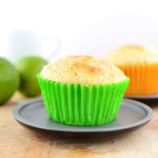 Side view of lime muffin in green paper case on grey plate with limes in background.