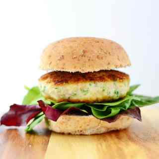 Side view of chicken burger with salad leaves on top of wooden table.
