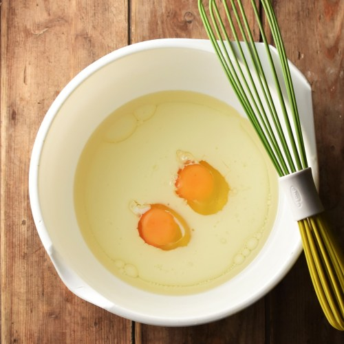 2 eggs with milk in large white bowl with green whisk.