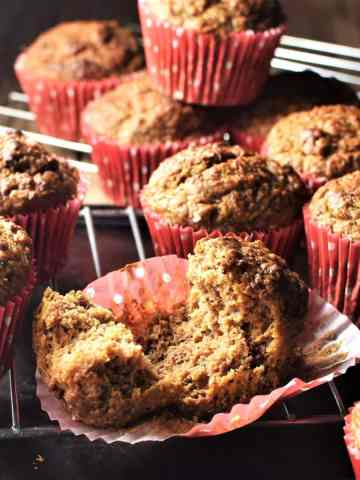 Side view of healthy carrot muffins in red liners on top of cooling rack.