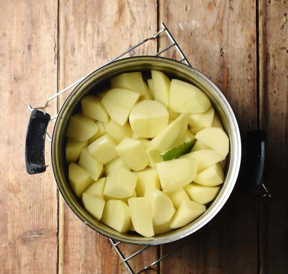 Peeled potato pieces with bay leaf in pot with water.